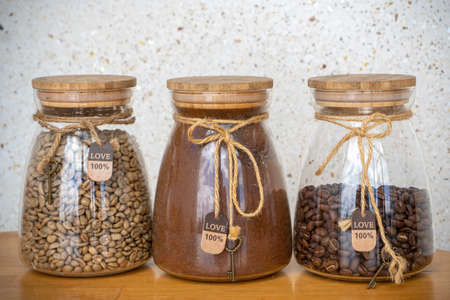 Coffee beans, ground coffee and green coffee in glass jars on a table. Фото со стока
