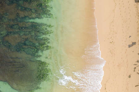 Sea waves and beautiful sand beach aerial view. Birds eye view of ocean waves