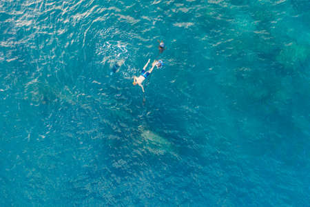 Three people snorkling in the ocean in Amed, Bali, Indonesia