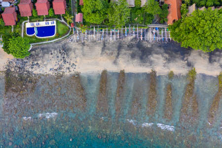 Coastline of Amed, Bali. Beach with stones and fishing boats. Aerial view.