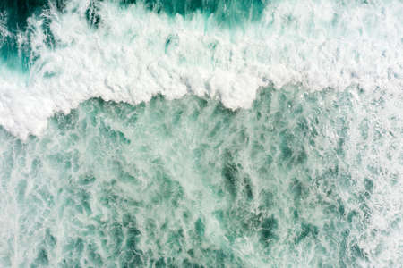 Top aerial view of giant ocean waves crashing and foaming.
