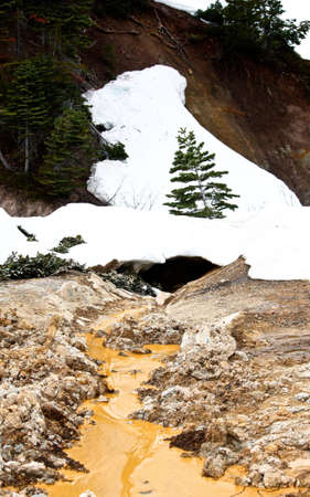 A small stream of boiling hot mud making its way from out of the snow-covered hill.