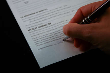 autograph: A great close up of a signing of a work document, isolated on black. Stock Photo