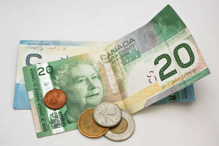 A close up of a selection of Canadian currency, including a 20 and a 5 dollar bill, a loonie, a twoonie, a quarter and a penny. Stock Photo