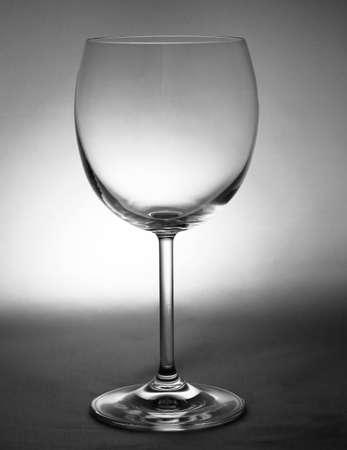 source: A single light source illuminating an empty glass of wine.