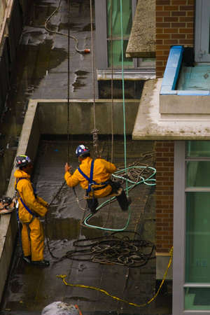 abseil: Two yellow-clad construction workers roping down a highrise.