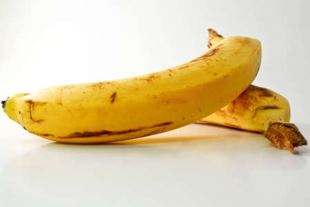 Two yellow bananas on a white background with natural shadows.