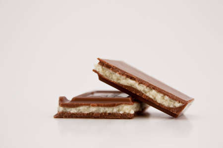Two pieces of milk chocolate on white with natural shadows. photo