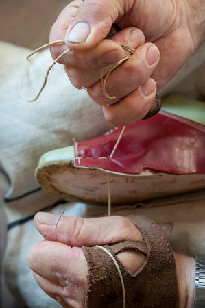 제화공은 구두를 정교하게 바느질한다. 스톡 콘텐츠
