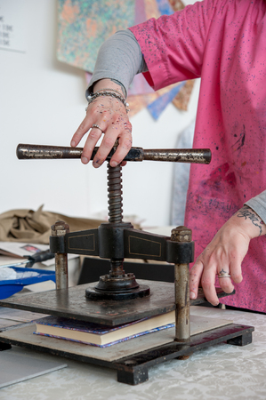 The bookbinder at the hand press, in his artisan shop