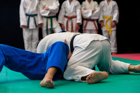 immobilize: Black belt in Judo immobilizes his opponent to the ground