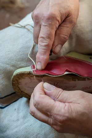 The shoemaker sews a shoe craftily, with twine and awl
