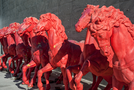 Red horses sculptures, in a row, on gray stones background