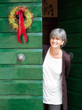 A smiling woman on the doorstep, with a Christmas wreath