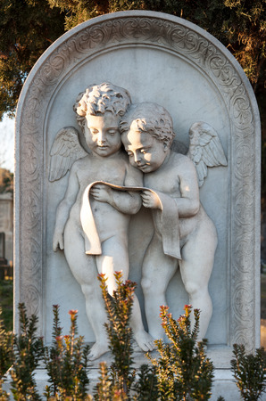 Little marble angels reading a prayer on a gravestone, illuminated by a ray of sunshine Stock Photo