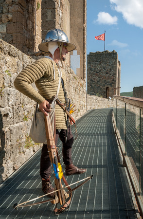 A sentry with crossbow watches the walls of the castle of Monteriggioni, Tuscany, Italy