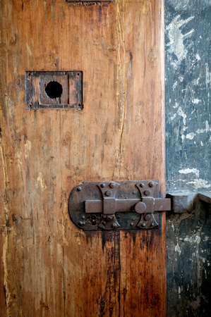 The big deadbolt on the wooden door of the prison cell Stock Photo
