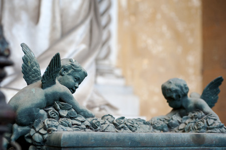 tombstones: Two cherubs climb a full of roses altar, glancing sideways Stock Photo