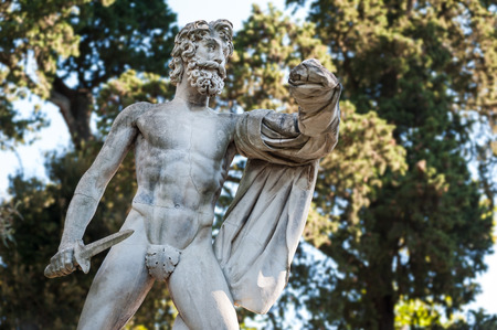 Florence, ITALY - July 18, 2017: The Greek Tyrantcidal statue, is a copy of the statue of Aristogitone (447 bC) by Kritios and Nesiotes. It is located in the Boboli Garden, along the main avenue. On white background. Stock Photo - 85175694