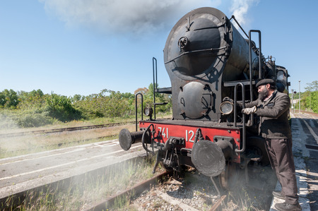 Steam locomotive stops on the tracks, snorting smoke and hot steam