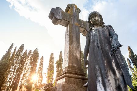 premature: The little girls statue premature dead, close to the the stone cross, at the cemetery