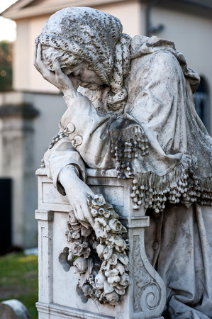 religious clothing: An old suffering woman statue cries on her knees onto the tombstone, holding a wreath