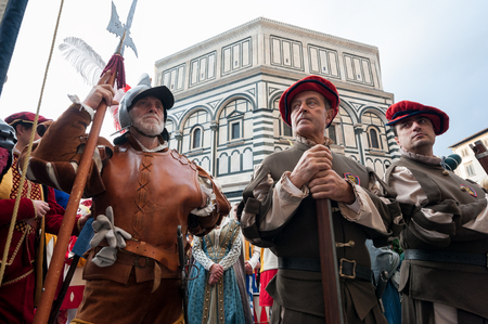 Florence, Tuscany, Italy - January 6, 2018: Extras in Renaissance soldiers costumes on the churchyard of Santa Maria del Fiore, during the historical recreation of the Procession of the Magi; Baptistery of Saint John on background