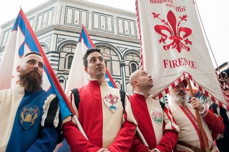 Florence, Tuscany, Italy - January 6, 2018: Florentine standard bearer with traditional clothes on the churchyard of Santa Maria del Fiore, during the historical recreation of the Procession of the Magi; Baptistery of Saint John on background