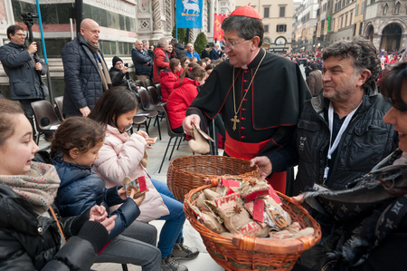 Florence, Tuscany, Italy - January 6, 2018: The Florentine Archbishop Cardinal Giuseppe Betori distributes gifts to the children to celebrate the Feast of Epiphany, during the historical recreation of the Procession of the Magi