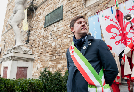 Florence, Tuscany, Italy - January 6, 2018: The mayor of Florence Dario Nardella with mayoral sash during a public ceremony. Behind him, the Palazzo Vecchio and the historical coat of arms of Florence.