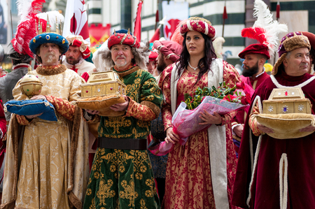 Florence, Tuscany, Italy - January 6, 2018: Three Wise Men and a Florentine noble woman, carrying gifts in the precious golden caskets, during the historical