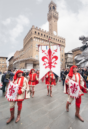 Florence, Tuscany, Italy - January 6, 2018: Standard bearer and trumpet player with historical coat of arms of Florence, parades in the Piazza della Signoria, during the historical recreation of the