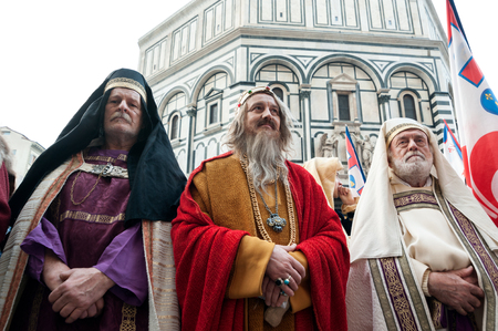 Florence, Tuscany, Italy - January 6, 2018: Three extras in medieval religious clothes on the churchyard of Santa Maria del Fiore during the historical recreation of the Редакционное