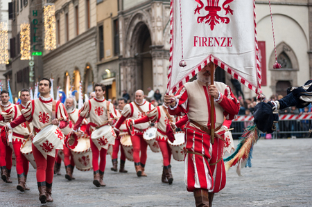 Florence, Tuscany, Italy - January 6, 2018: Standard bearer and drummer in traditional red and white costumes, with historical coat of arms of Florence, parades in the Piazza Duomo, during the historical recreation of the Редакционное
