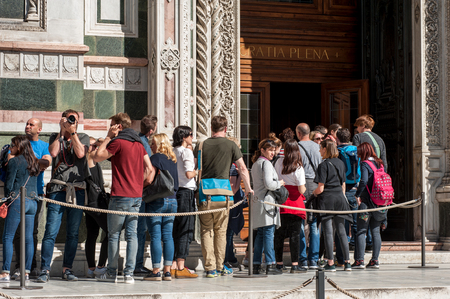 Florence, Italy - April 7, 2018: Tourists queue waiting at the entrance of Santa Maria del Fiore Cathedral, in Florence. Editorial