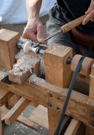 An artisan carves a piece of wood using a manual lathe