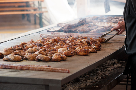 Man grilling an assortment of meat and chiken on a large barbecue Stock Photo