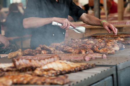 Man grilling an assortment of meat and chiken on a large barbecue Stock fotó - 116534248