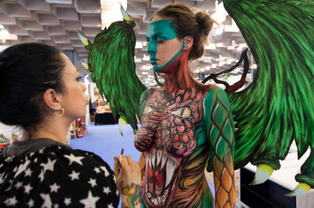 Florence, Italy - April 24, 2018: Bodypainting artist with her beautiful model, creates a Fantasy creatures, at the ? ?? Exhibition of handicraft 2018?? , in Florence.