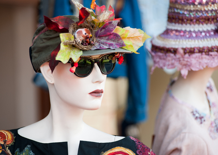 Mannequin with coloured fashioned hat and sun glasses at the market flea