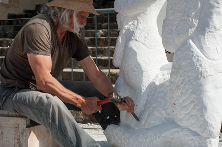 Senior sculptor working outdoor on his marble sculpture in his workshop with hammer and chisel