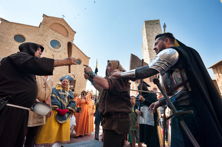 San Gimignano, Siena, Italy - 2018, June 17: Extras in action during an historical medieval reenactment: sentenced to death by beheading. The priest blesses the condemned before the execution.