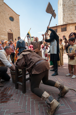 San Gimignano, Siena, Italy - 2018, June 17: Extras in action during an historical medieval reenactment: sentenced to death by beheading. The executioner raises the ax.