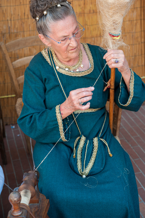 Old woman in medieval clothes demonstrating traditional wool spinning.