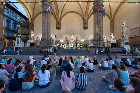 People sitting on the pavement of the Piazza della Signoria, participating in an open-air concert at the Loggia dei Lanzi, Florence, Italy.