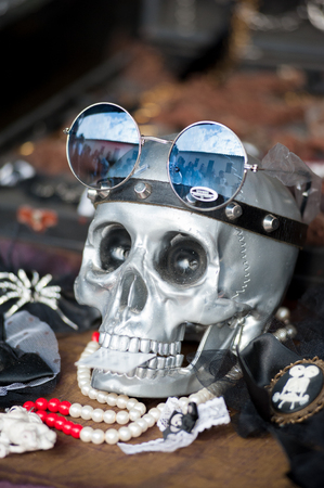 A silver skull with glasses and other fashion accessories on a vintage market stall.