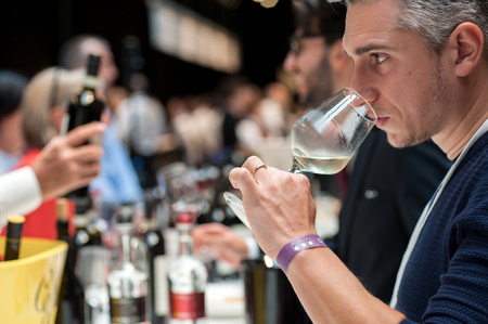 Closeup portrait of young male customer smell white wine during a wine tasting event