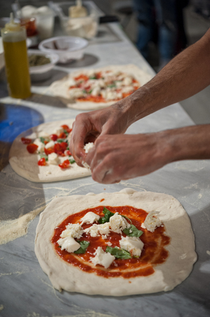 Margherita pizza preparation on a marble countertops. Pizzaiolo puts pieces of mozzarella and basil leaves over a pizza dough with tomato sauce. Selective focus