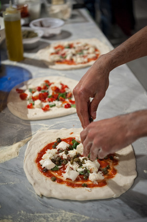 Margherita pizza preparation on a marble countertops. Pizzaiolo puts pieces of mozzarella, capers and basil leaves over a pizza dough with tomato sauce. Selective focus