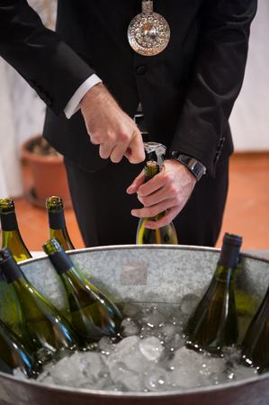 sommelier opening wine bottle with corkscrew. Big metal ice bucket with bottles in the foreground. Stock Photo